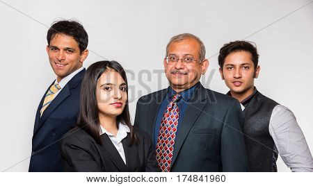 Group of four good looking Indian business people or lawyers. Business team or delegation from India. standing isolated over white background