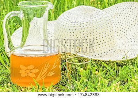 White hat and carafe of juice on the green grass in the spring garden close-up