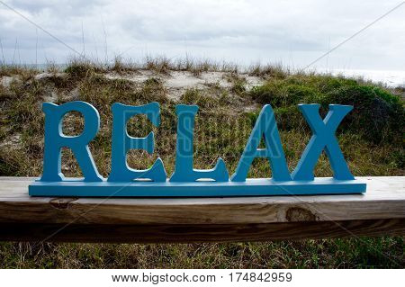 Relax Sign with Sea Berm and Sky in the Background