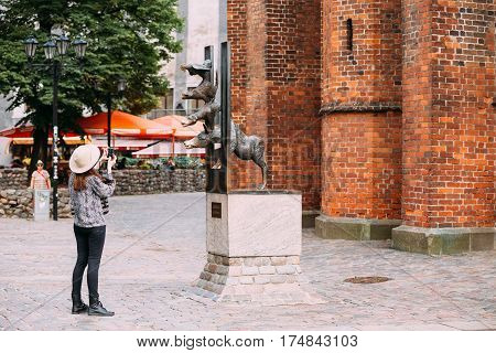 Riga, Latvia - July 1, 2016: Young Girl Tourist Photographing Bronze Statue Of The Bremen Town Musicians Located In Riga, Latvia. Famous Landmark. Travel Destination