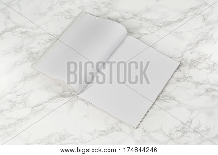 Mock-up magazine or catalog on white marble table. Blank page or notepad on stone background. Blank page or notepad for mockups or simulations.