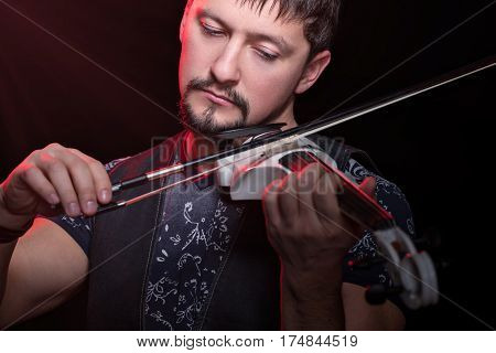 Young bearded man playing a white electric violin, isolated on a black background