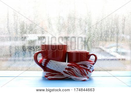 big and small red cup wrapped in a scarf on window background with drops after the rain / warming gentle hugs hot couple