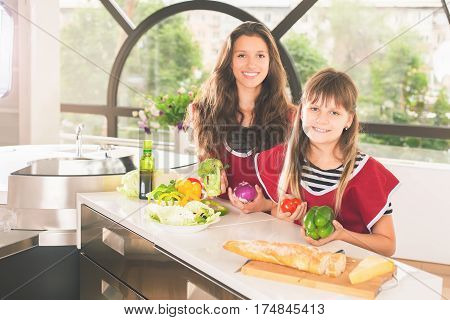 Happy family of young girls cooking. Vegetarian meal at kitchen. Funny sisters making salad. Healthy lifestyle. Recipe of vitamins nutrition. Girls looking at camera