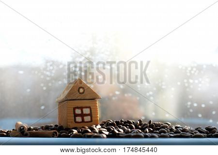 toy house on the hill of beans in the background window with raindrops / cozy place for coffee break