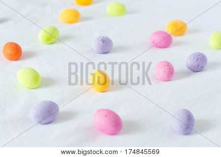 Spring colorful easter eggs scattered around a white sheet
