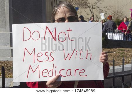 Asheville North Carolina USA - February 25 2017: Older woman holds a sign at an Affordable Care Act (ACA) demonstration telling politicians