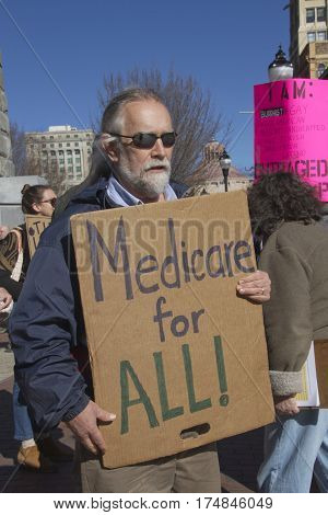 Asheville North Carolina USA - February 25 2017: Older man holds a sign saying