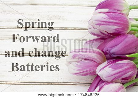Spring Forward message A bouquet of purple tulips on weathered wood with text Spring Forward and change Batteries