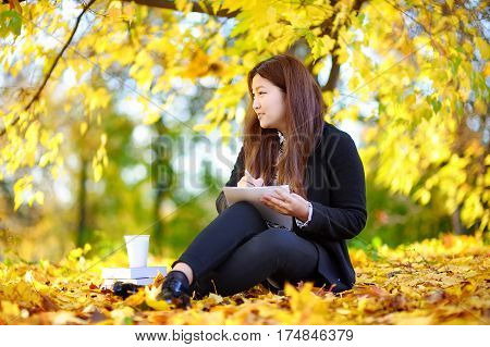 Young Asian Woman Studying/working And Enjoying Sunny Autumn Day
