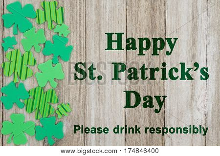 Saint Patrick's Day safety message Green shamrocks on weathered wood with text Happy St Patrick's Day Please drink responsibly