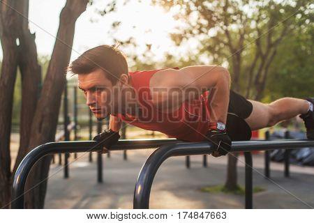 Fit young man doing push ups on horizontal bar outdoors