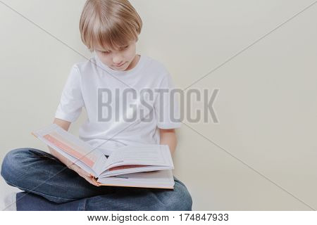 Education, school, leisure concept. Little boy sitting and reading book