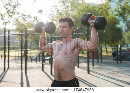 Muscular male athlete with arms raised doing lifting exercises with dumbbells