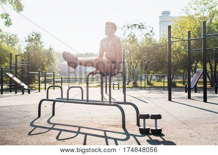 Young strong athlete working out in outdoor gym, doing leg lifting abs exercise
