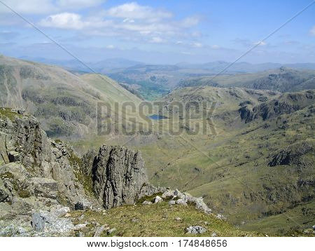 Looking down to Styhead Tarn from Lingmell Fell in the English Lake District with mountains surrounding the tarn and rocks in the foreground
