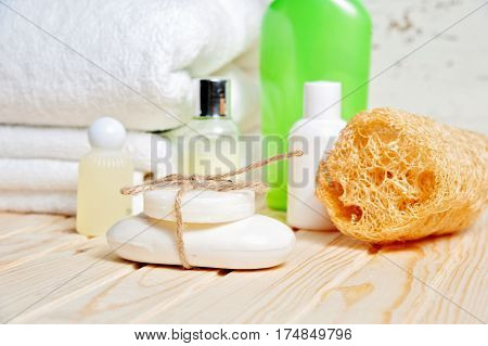 Bathroom accessories and white towel. Soap and lotion. Beauty care accessories for bath. White background. Closeup.