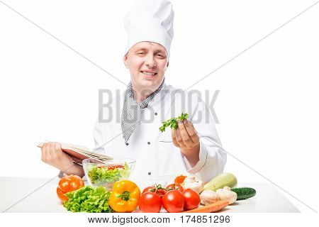 Cook Happy Face At The Table With Salad And A Book Of Recipes On A White Background
