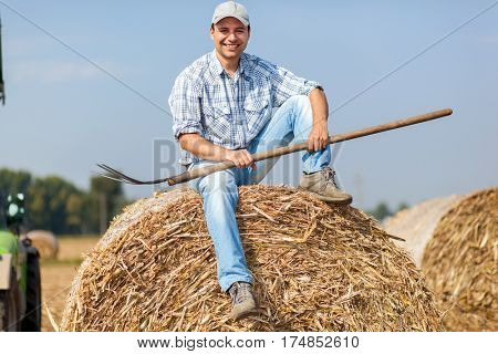 Portrait of a smiling farmer holding a pitchfork