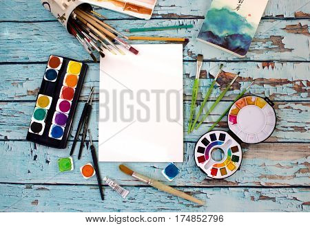 Watercolors, color pencils and sketchbook top view on blue old rustic wooden table. Flat lay styled photo mockup, workplace on aquarelle artist.