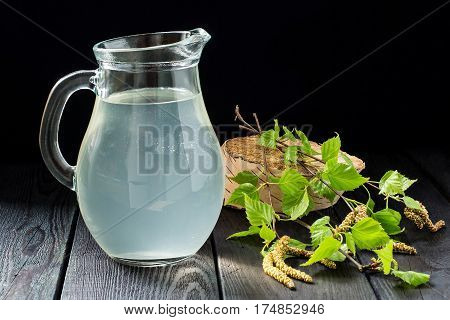 Spring useful vitamin drink. Fresh cold birch juice in a jug and birch branches on a dark background. Concept of healthy and vitamin food