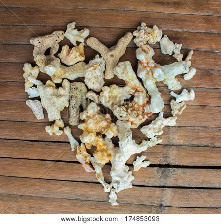 Heart from white corals on wooden background. Handmade love decor from beach finding. Multicolored ornament for Valentine Day greeting. Nature care heart seaside decor. Marine heart on grungy backdrop