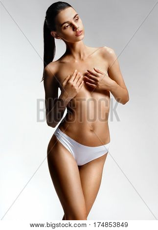 Young girl with clean skin nude topless breasts. Beautiful girl covering her nude breast. Health and beauty concept