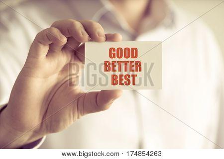 Businessman Holding Good Better Best Message Card