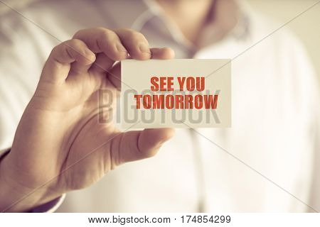 Businessman Holding See You Tomorrow Message Card