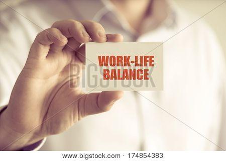 Businessman Holding Work-life Balance Message Card