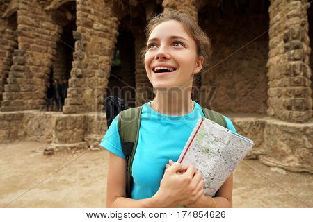 Travel in Spain. Enthusiastic girl holding travel map in her hands looking up. Sightseeing. Hiking.