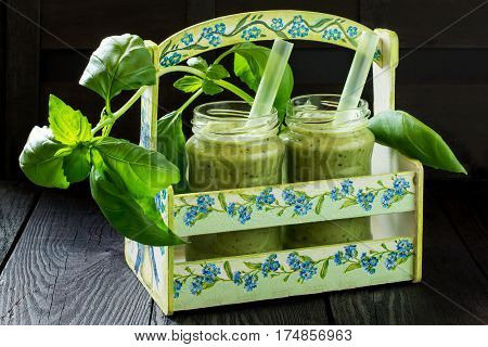 Jars of vitamin green smoothie in a box and sprig of basil on a wooden table. Concept of healthy or vegetarian food