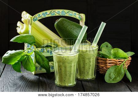 Glasses of vitamin green smoothie in the box and ingredients for cooking on a wooden table. Concept of healthy or vegetarian food