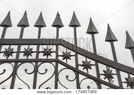 Part of the forged lattice of a black iron fence with arrows stars and hearts