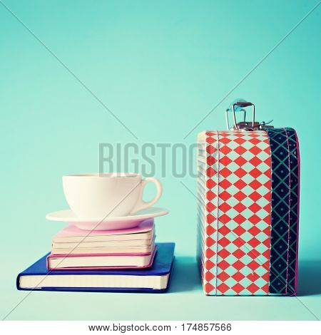 Vintage lunchbox and cup of coffee over notebooks