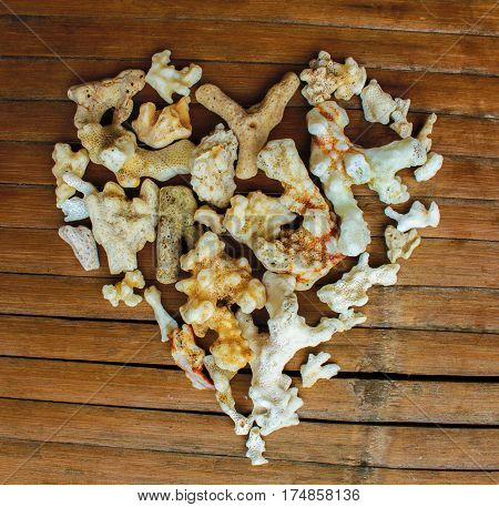 Heart from white corals on wooden background. VIntage love decor from beach finding. Multicolored ornament for Valentine Day greeting. Nature care heart seaside decor. Marine heart on grungy backdrop