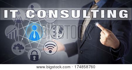 Male corporate advisor in blue business suit is activating IT CONSULTING onscreen. Information technology metaphor and business concept for IT advisory services and computer consultancy.