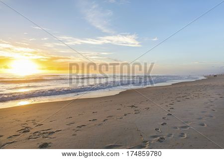 Colourful beach sunrise with footprints in the sand at Surfers Paradise, Gold Coast.