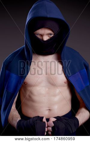 Man practicing martial arts hid his face behind a mask. Boxer on a dark background