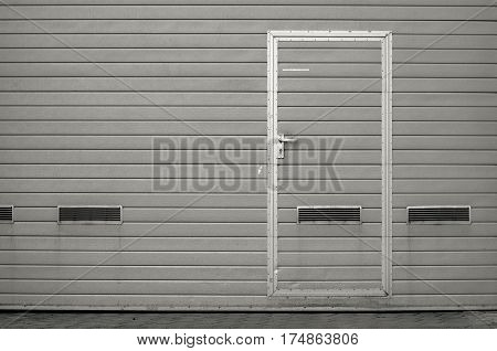 Gray garage gate with ventilation grilles. Large automatic up and over garage door with inclusion of smaller personal door. Multicolor background set