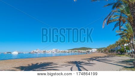 St Antoni de Portmany, Ibiza.  Row of palms lines the beach.  In the distance in the water a man paddles a sailboard toward an abandoned sailboat, stranded on shore.