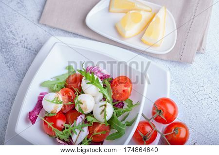 Fresh mozzarella balls served with spicy rocket leaves and cherry tomatoes.