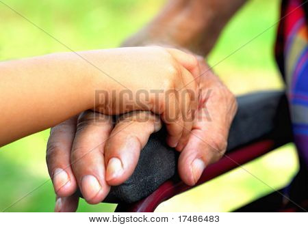 little girl holding hard a handicapped man`s hand