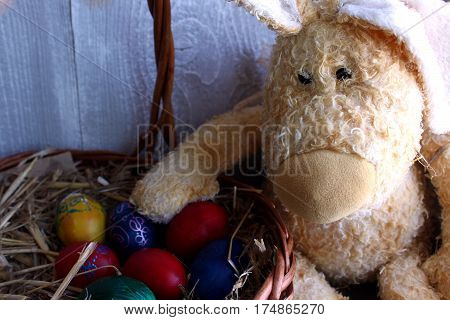 Colored Easter Eggs In The Basket And Easter Bunny
