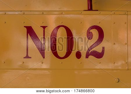 Red Number 2 on Yellow Metal Background