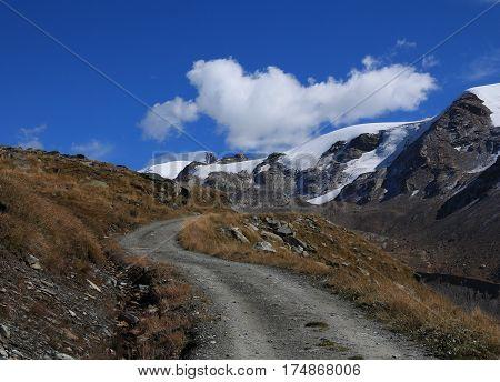 Scene on the way to Fluhalp. Curved gravel road. Findel glacier. Landscape in Zermatt.