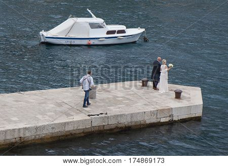 DUBROVNIK, CROATIA - OCTOBER 18, 2016:  Groom and bride posing on the pier of old town in cold evening