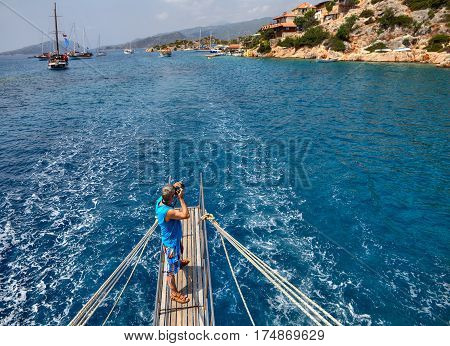 Antalya Turkey - 28 august 2014: The tourist photographs the village of Kalekoy on the island of Kekova standing on the gangways of the stern of a cruise boat.