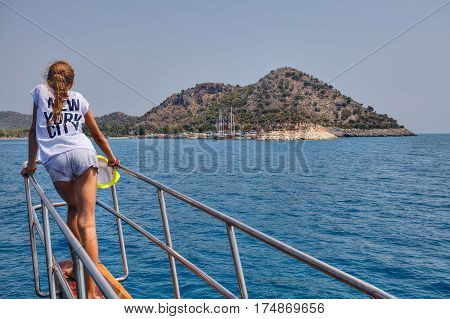 Antalya Turkey - 28 august 2014: One unknown teenager girl looks towards the harbor standing on the nose of a sightseeing boat.