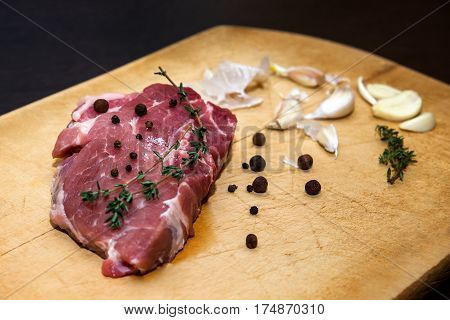Beef steak. Raw marble beef on a cutting board. On a black background for text design or restaurant menus. Food background. Horizontal photo.
